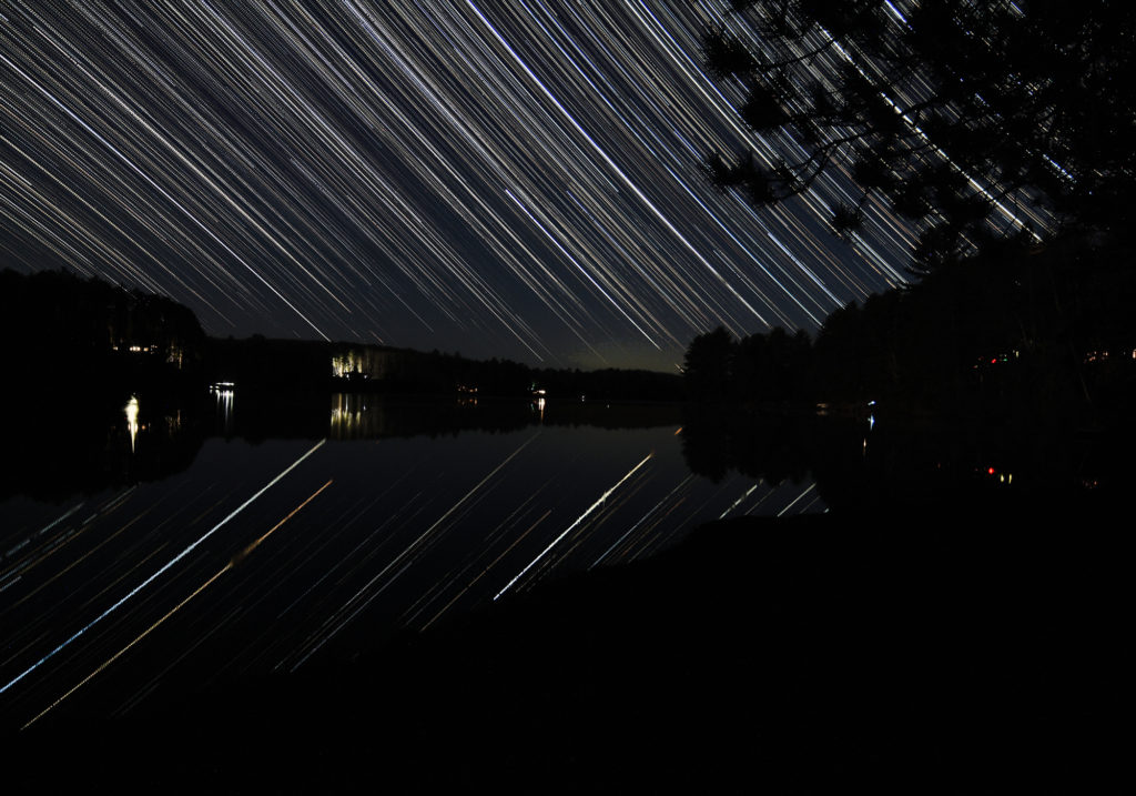 Star trails reflect in a calm lake in Canada